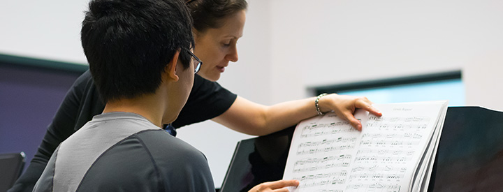Instructor looking over sheet music with student