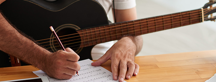 Man holding guitar and writing on music notation paper