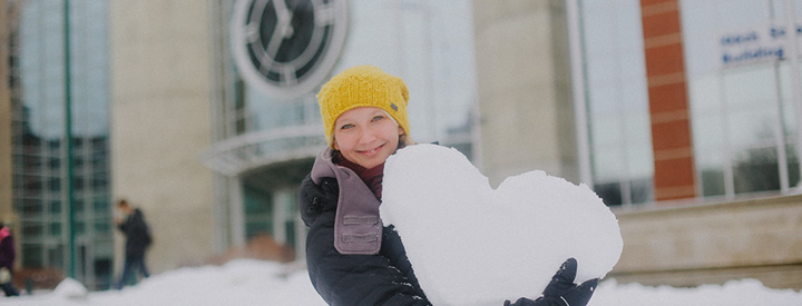 Female student holding heart shaped snow ball in front of MacEwan campus