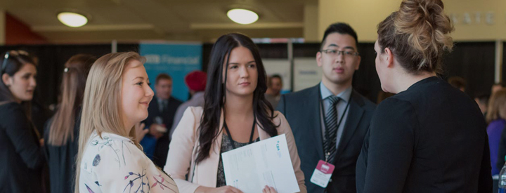 MacEwan University students speaking with a potential employer at a Career Fair