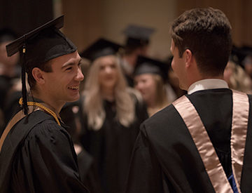 Two male students in grad gowns