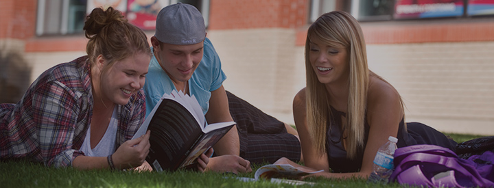 Students reading on grass outside MacEwan
